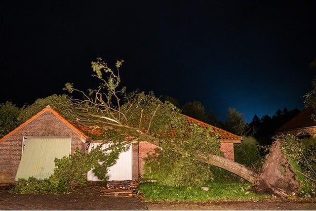 Tornádo na severu Německa. Spadlý strom na garáž u domu.